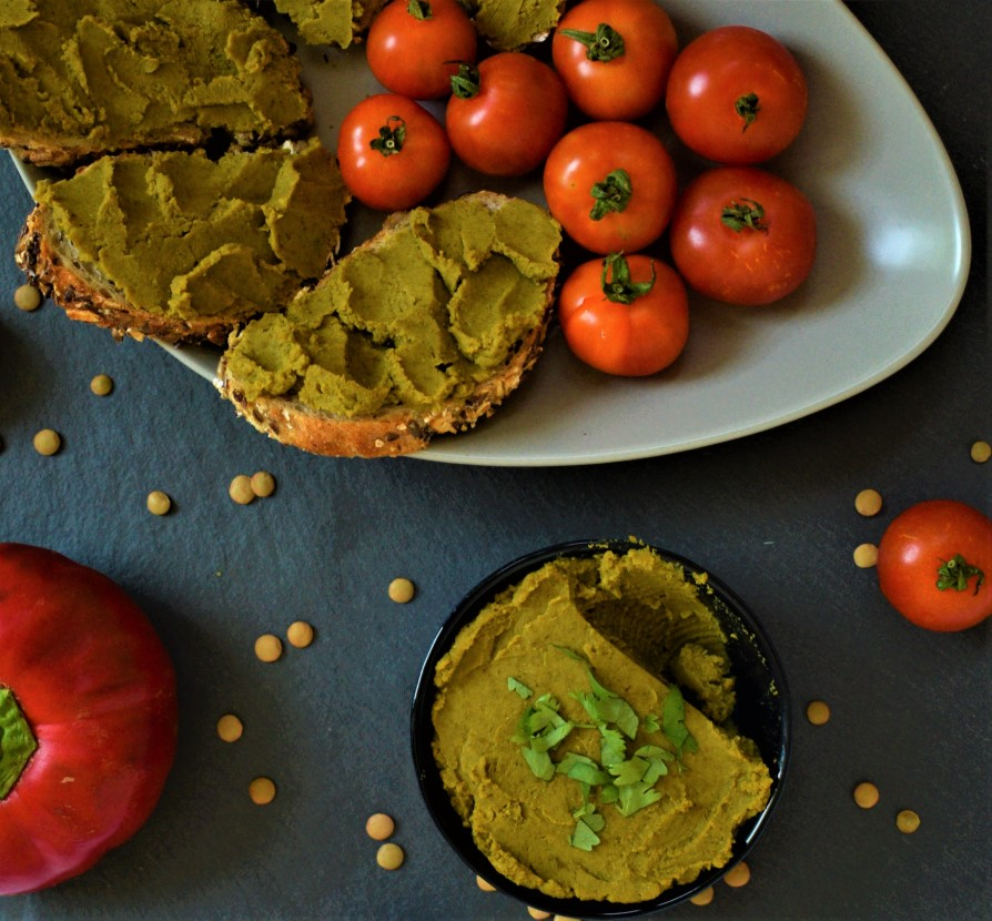 Green lentil paté spread on bread slices and served with vegetables