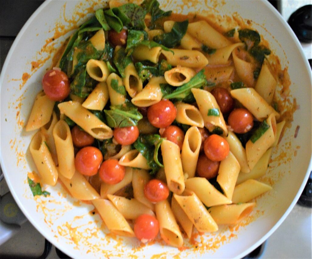 Cooking pasta with spinach and cherry tomatoes
