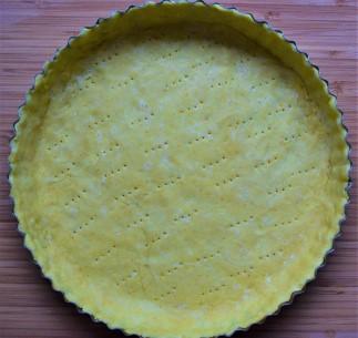 Quiche dough in the tart tin, prepared for baking