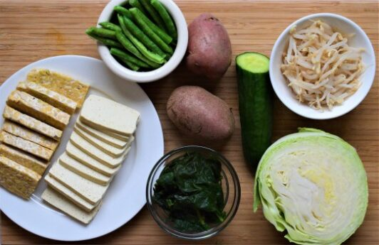 Gado gado salad ingredients - tempeh, tofu, spincah, potatoes, cabbage, green beans, cucumber and bean sprouts
