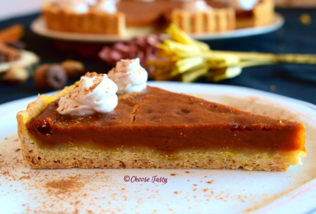 Slice of pumpkin coconut pie decorated with coconut whipped cream and cinnamon