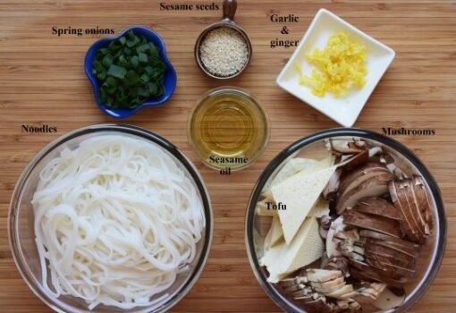 Stir fry ingredients: rice noodles, mushrooms, tofu, sesame oil, minced garlic and ginger, sesame seeds, spring onion