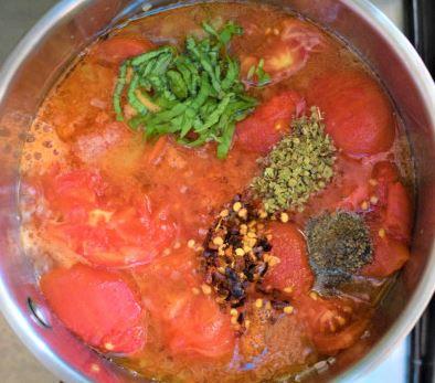 Homemade marinara sauce preparation with blanched tomatoes, fresh basil, chili flakes