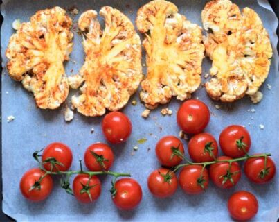 Spiced cauliflower steaks and cherry tomatoes ready to bake