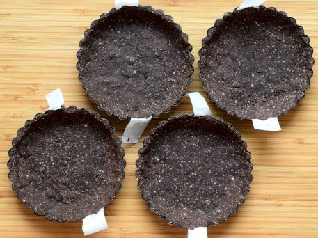 Chocolate crust pressed into the tart pans