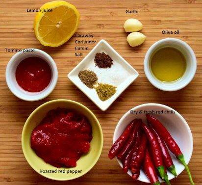 Harissa ingredients: red chilies (fresh and dried), roasted red peppers, tomato paste, lemon juice, garlic, olive oil, caraway, cumin, coriander, salt